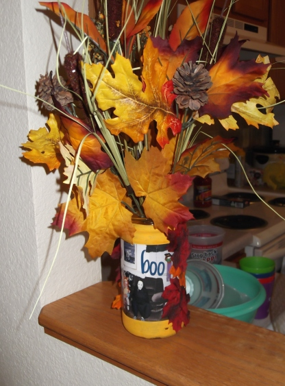 I made this from a recycled jar spaghetti sauce, painted it, pasted a Halloween photo of my kids, and glued some Fall leaves on it.